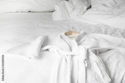 Photo white bath robe on the bed in hotel room