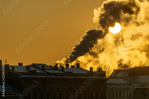 Foto  steam thick from the cold and lit by a huge round low sun rising above the historic center of St