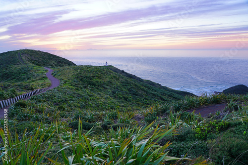 Tuinposter Purper Sunset over Cape Reinga (Te Rerenga Wairua), the northwesternmost tip of the Aupouri Peninsula, at the northern end of the North Island of New Zealand, where the Tasman Sea meets the Pacific Ocean