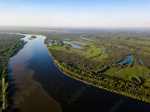Deurstickers Zwart Ob river flows through the taiga. River landscape, beautiful sky reflection in water. Vasyugan Swamp from aerial view. Tomsk region, Siberia, Russia