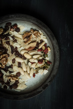 View Form The Top, On A Black, Rustic, Wooden Table Stands A White Plate With Hand-painted Black Edges Full Of Various Nuts