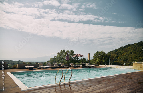 Fototapety, obrazy: Swimming pool with sunbeds and sun umbrella and mountains in the background.
