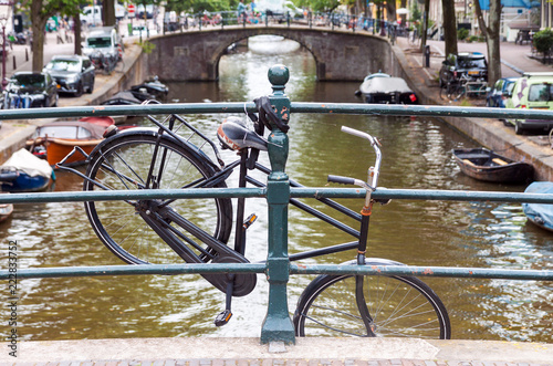 Photo  Old abandoned bicycle hanging on bridge railing in Amsterdam, Netherlands