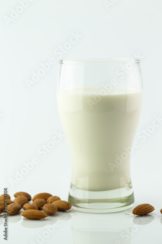 Fotografia  Almond milk in glass with almonds seed on white background