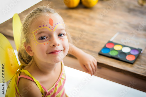 Cute little girl with face paint sitting at a table, looking at camera smiling. Halloween party or carnival family lifestyle background. Face painting and dressing up.