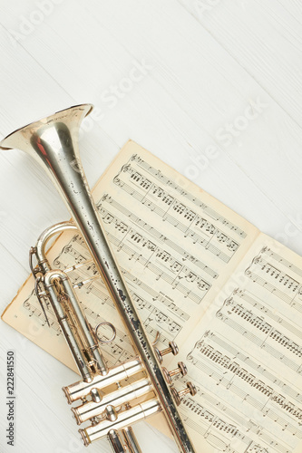 Rusty trumpet on musical notes, top view Fototapeta
