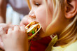 children, diet, culinary and food concept .Young blonde girl eating tortilla with meat and vegetables, mexican traditional snack concept