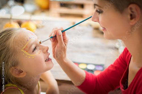 Young mother painting daughters face for Halloween party. Halloween or carnival family lifestyle background. Face painting and dressing up.