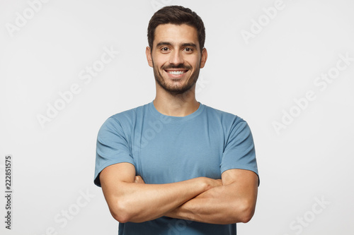 Pinturas sobre lienzo  Smiling handsome man in blue t-shirt standing with crossed arms isolated on gray