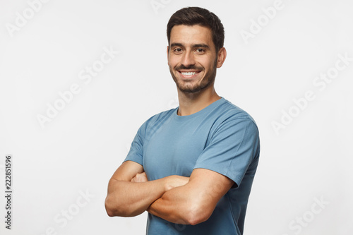 Fotografie, Tablou Portrait of attractive young sporty man in blue t-shirt standing with crossed ar
