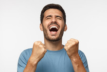 Young Man Isolated On Gray Background Shouting With Closed Eyes, Celebrating Victory, Squeezing Fists In Deep Emotional Expression Of Happiness And Luck