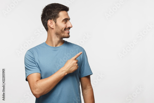 Casual dressed young man in blue t-shirt looking right, pointing with his finger Fototapeta