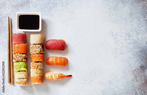 Sushi set, soy sauce and chopsticks on grey stone background