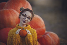 Cozy Autumn Photo Of A Girl With Pumpkins In A Yellow Sweater And Glasses. Stylish Young Woman In Autumn Decorations Holding A Small Pumpkin.