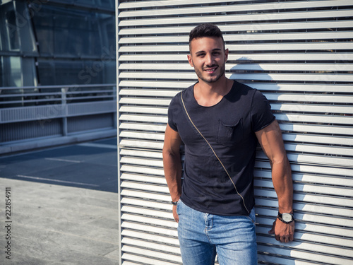 d2915f94 One handsome young man in urban setting in European city, wearing jeans and  black t