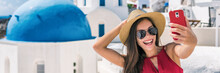 Happy Tourist Taking Selfie Having Fun On Europe Summer Vacation In Santorini, Cruise Destination Panoramic Banner. Asian Woman Panoramic Banner Holding Mobile Taking Picture.