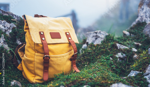 Fototapeta Hipster hiker tourist yellow backpack on background green grass nature in mountain, blurred panoramic landscape, traveler relax holiday concept, view wayroad in trip vacation, travel adventure obraz