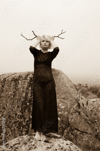 Fotografía  Artistic photo of a blond girl in black dress and sinister aesthetics on the rocks in the countryside on a cloudy day