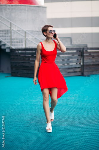b556746ae026 Young sexy woman wearing in red dress with deep neckline and sunglasses