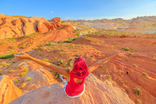 Freedom Hiking Woman At Valley Of Fire State Park On Top Of Fire Wave At Sunset. Happy Hiker Enjoying Panoramic Views Of Ribbons Of Red Rock Slice Through The Desert Landscape. Nevada, United States.