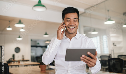 Fotografie, Obraz  Smiling Asian businessman using a cellphone and tablet at work