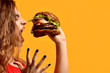 canvas print picture - Woman hold big beef burger sandwich with hungry mouth happy screaming laughing on yellow background