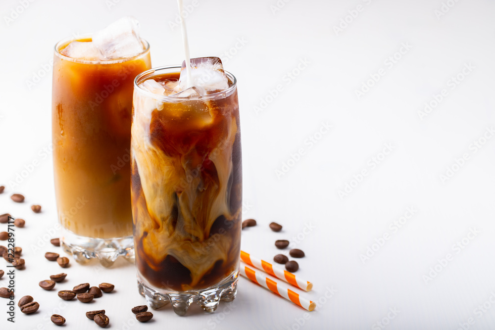 Photo  Ice coffee in a tall glass with cream poured over and coffee beans