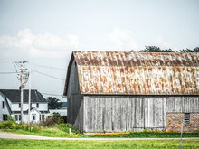 Beautiful Photograph Of A Weathered Old Barn With Rusted Tin Roof And Gray Wood And Adjacent Farm House With White Fluffy Clouds In The Blue Sky Above.