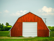 Beautiful Photograph Of A Freshly Painted Red Vintage Weathered Wood Barn With Pitched Roof In A Field With Blue Sky And White Fluffy Clouds Above.
