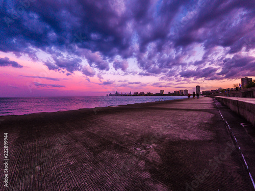 Fotografie, Obraz  Chicago, IL - May 9th 2018: People flock to the lakefront to catch the gorgeous sunset over the Chicago skyline after earlier storm clouds drift out across the water