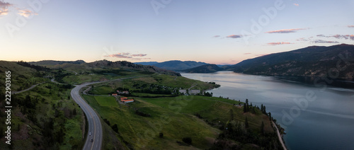 Aerial panoramic view of a highway near Kalamalka Lake during a vibrant summer sunset Canvas-taulu