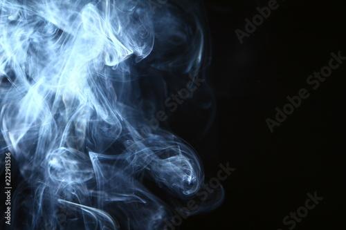 Fotobehang Rook marvellous swirl glowing blue smoke on dark background.