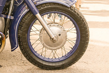 Motorcycle Front Wheel With Shiny Chrome Knitting Needles With Blue Rim Close-up On The Asphalt Background