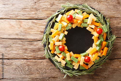 Assorted pesto cheese, cheddar, Mimolette with tomatoes and rosemary in the form of a wreath close-up. horizontal top view