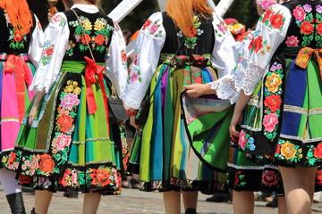 Dziewczyny w regionalnych tradycyjnych strojach łowickich idą w proceji Bożego Ciala w Łowiczu