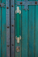 An Old Green Closed Door With Large Door Handles And A Keyhole
