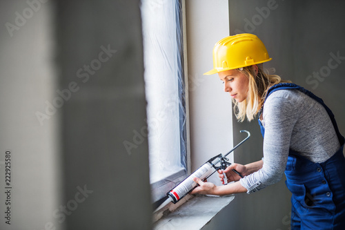 Obraz Young woman worker using silicone sealant gun on the construction site. - fototapety do salonu