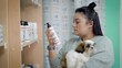 young female pet owner is choosing shampoo for her dog in a shop, holding cute shih tzu puppy on hands