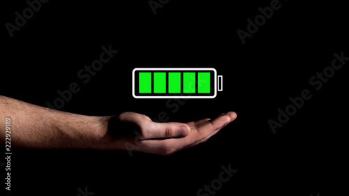 Hand showing Battery Charge icon on black background Canvas Print