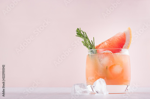 Foto op Canvas Cocktail Cold grapefruit alcohol cocktail in misted glass with rosemary and grapefruits slice on pastel fashion pink background.