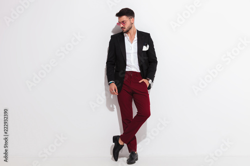 Fotomural relaxed elegant man leaning against wall looks down to side