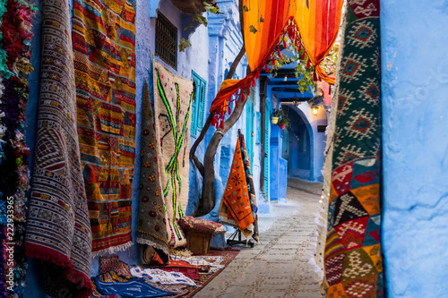 Poster Maroc Traditional carpets in colorful narrow street of Chefchaouen in Morocco