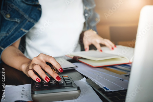 Photo businessman working with calculator and digital tablet computer with financial business strategy layer effect in office, bookkeeper and auditor concept