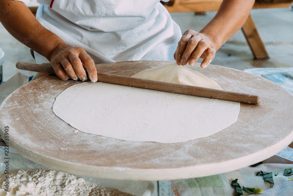 Fototapeta Woman rolls out dough, Turkish traditional flat cakes.