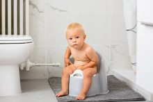 Child Sitting On Potty. Kid Pl...