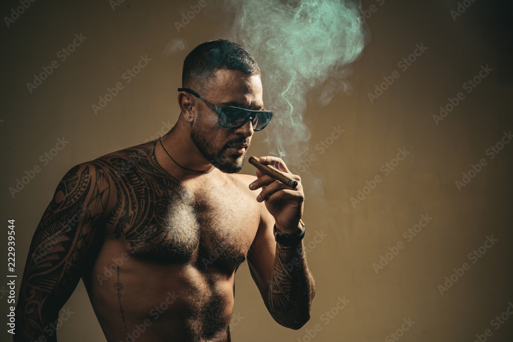 Fototapeta Tattooed man with cigar. Cigar smoking enjoy life and moment. Portrait of a bearded businessman with a beautiful torso smoking a cigar and drinking whiskey. Cuban cigars. Copy space