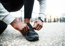 A Close-up Of A Young Sporty Black Man Runner Tying Shoelaces Outside In A City.