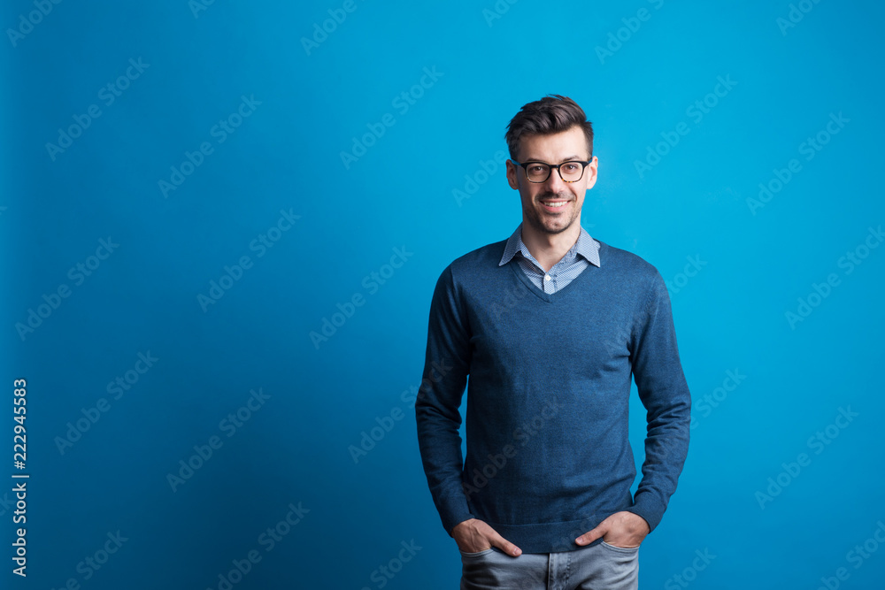 Fototapety, obrazy: Portrait of a young man with glasses in a studio on a blue background.