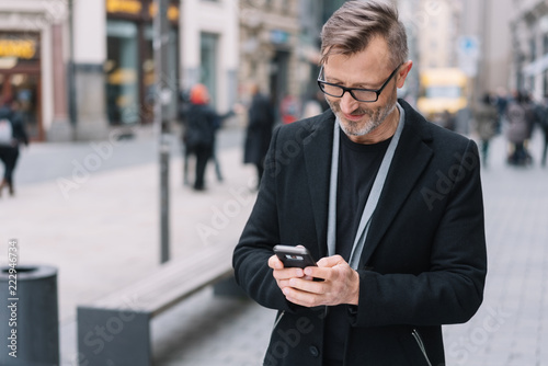 Valokuva  Street portrait of smiling mature man with phone