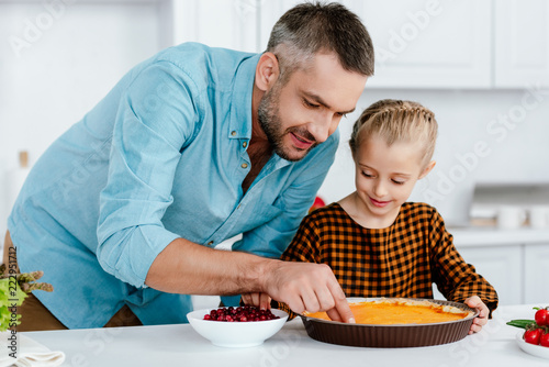 Leinwand Poster happy father and adorable little daughter decorating pumpkin pie for thanksgivin